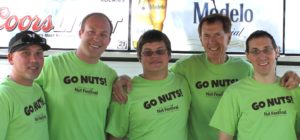 "five men wearing green shirts that say ""go nuts"" posing for a photo at the Kern County Nut Festival"